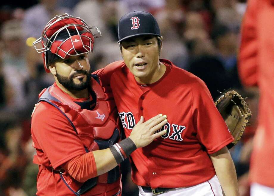 Red Sox catcher Sandy Leon and closer Koji Uehara celebrate after beating the Rays on Friday. Photo: Elise Amendola — The Associated Press   / AP