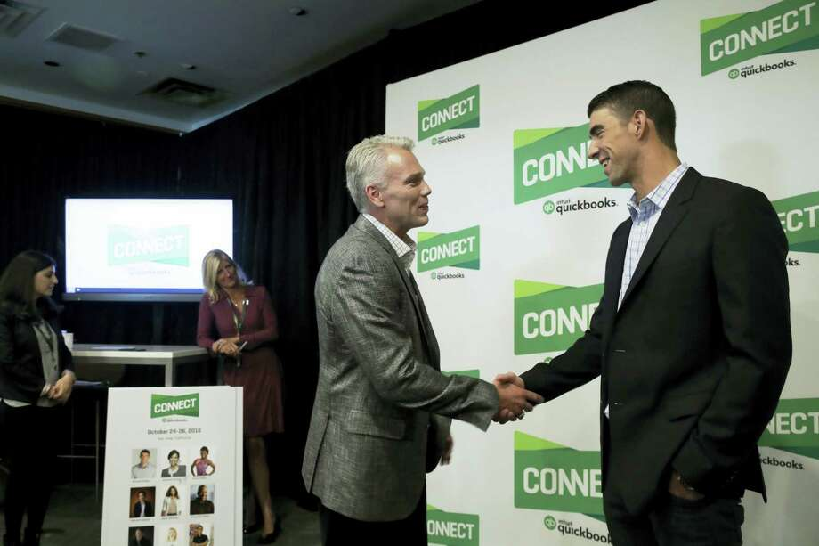 Former Olympic swimmer Michael Phelps, right, shakes hands with Intuit Chairman and CEO Brad Smith in San Jose. Photo: Marcio Jose Sanchez — The Associated Press   / Copyright 2016 The Associated Press. All rights reserved.