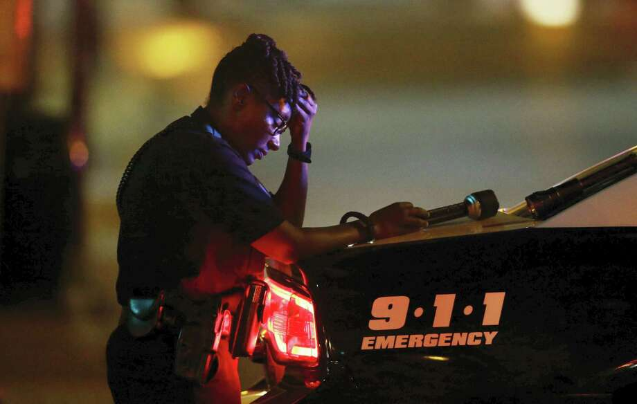 A Dallas police officer, who did not want to be identified, takes a moment as she guards an intersection early Friday after a shooting in downtown Dallas. Photo: The Associated Press   / Copyright 2016 The Associated Press. All rights reserved. This material may not be published, broadcast, rewritten or redistribu