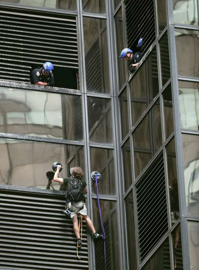 A man scales the all-glass facade of Trump Tower on Wednesday in New York City. A police spokeswoman says officers responded to Donald Trump's namesake skyscraper on Fifth Avenue in Manhattan. Photo: AP Photo — Julie Jacobson / Copyright 2016 The Associated Press. All rights reserved. This material may not be published, broadcast, rewritten or redistribu