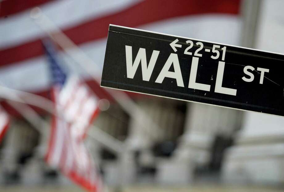 FILE - This May 11, 2007, file photo shows a Wall Street sign near the flag-draped facade of the New York Stock Exchange.   Global stocks mostly fell Wednesday, Aug. 10, 2016, amid quiet summer trading and questions about the sustainability of some indexes' rise to record highs. Photo: Richard Drew — The Associated Press  / AP