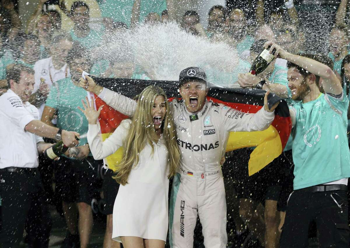 Mercedes driver Nico Rosberg of Germany, center right, is sprayed with champagne by his team after becoming the 2016 world champion in Abu Dhabi, United Arab Emirates.