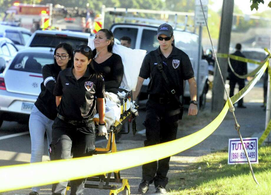 A woman who was on the ground is taken away after a plane crash on Main Street in East Hartford on Tuesday. Authorities said one person is dead and another is injured after a small airplane crashed near the Connecticut River.   Jim Michaud — Journal Inquirer via AP Photo: AP / Journal Inquirer
