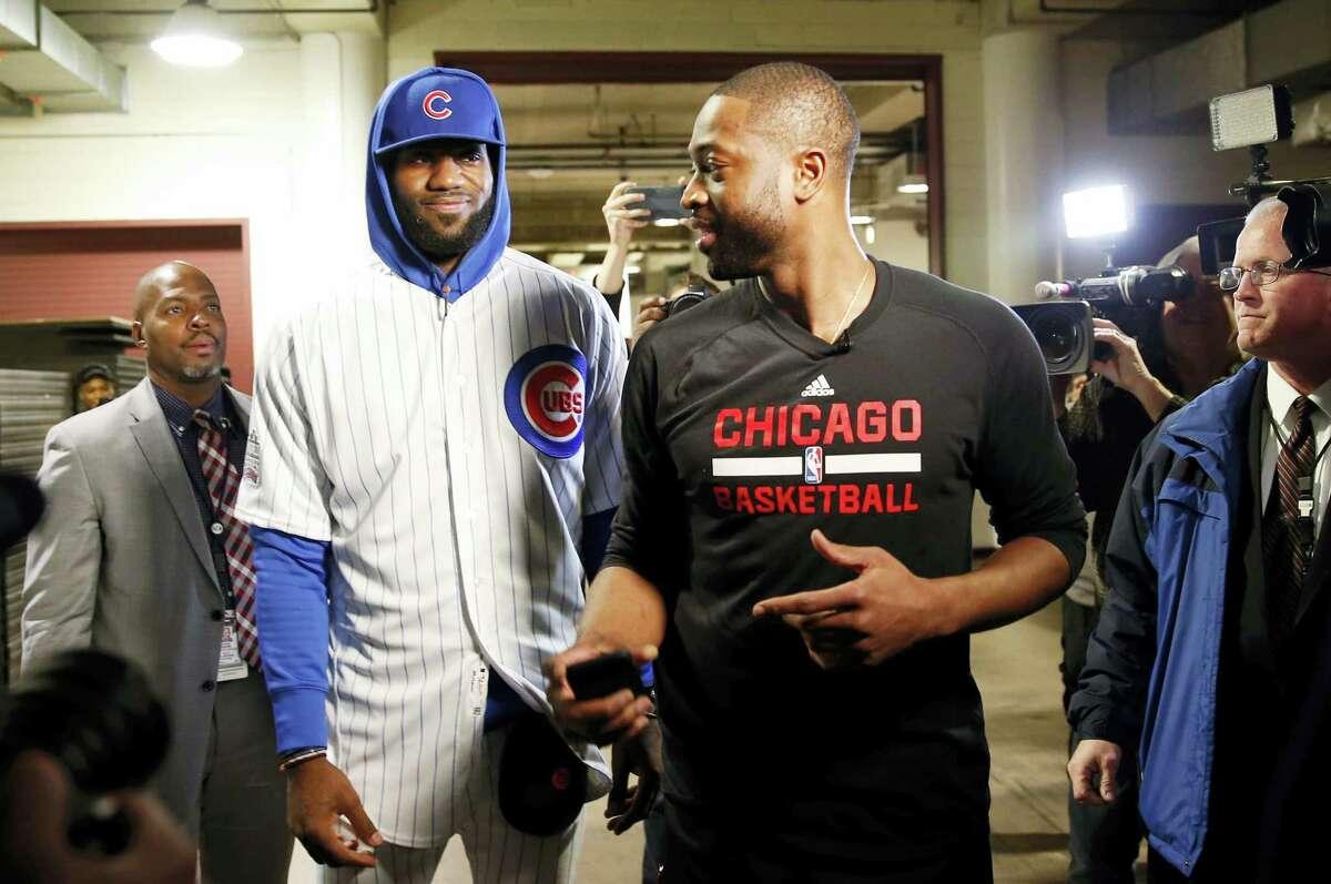 LeBron James, front left, talks with Dwyane Wade.