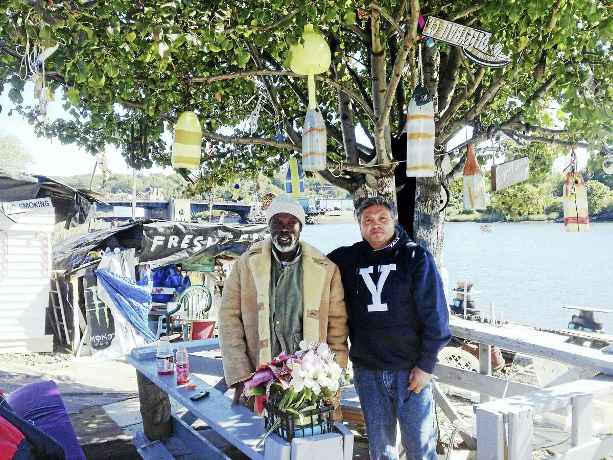 Curtis Libert and his friend Atroito Velez, longtime fishermen, at the site where Libert has set up comfortable chairs and keeps the area and waterfront clean and inviting to visitors at Poplar Street.