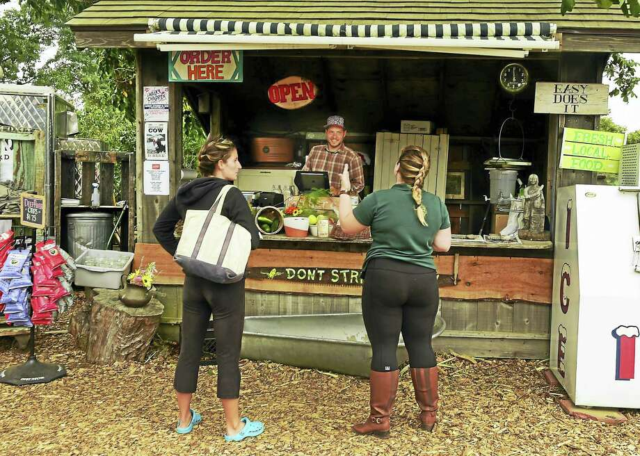 """""""Celestial Crop Tender"""" Andrew Biagiarelli, the farm market manager with customers at The Stand. Photo: Peter Hvizdak — New Haven Register   / ©2016 Peter Hvizdak"""