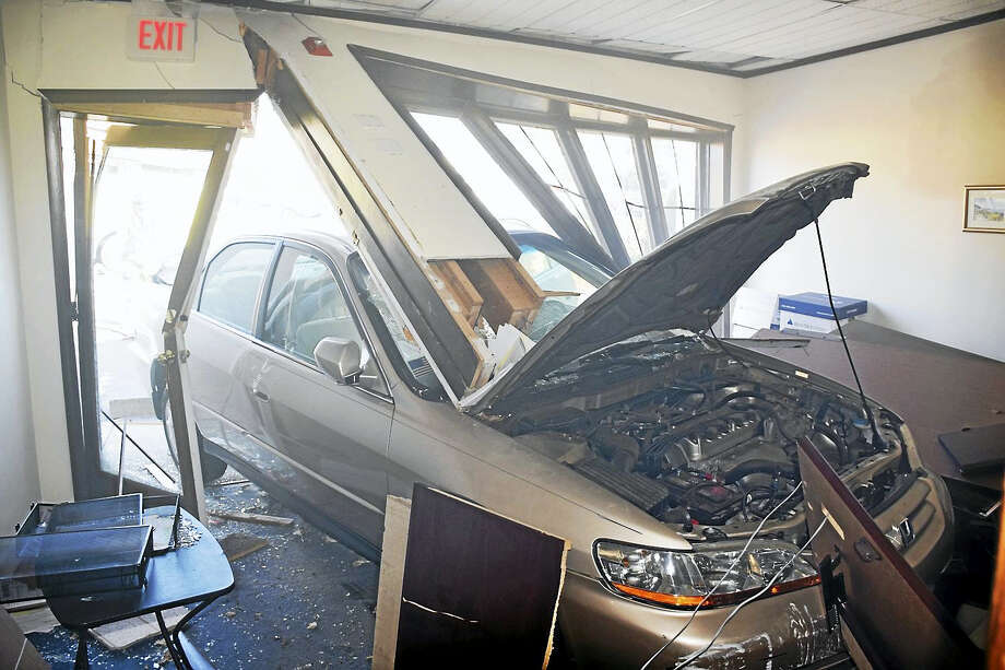 One person was hurt Tuesdy morning after crashing a car into a building at 250 Broad St. One person was in the building but was not injured. Photo: Courtesy Of Milford Fire Department