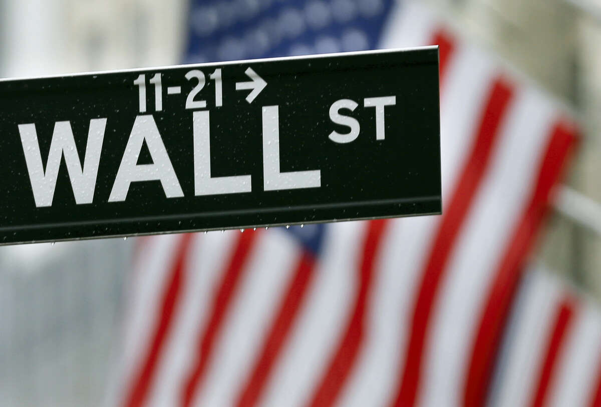 This July 9, 2015 photo shows a Wall Street sign near the New York Stock Exchange in New York. Stocks are opening solidly higher on Wall Street after the government reported an encouraging burst of hiring last month. The gain of 287,000 jobs in June, which the Labor Department reported early Friday, July 8, 2016 was far more than economists were expecting.