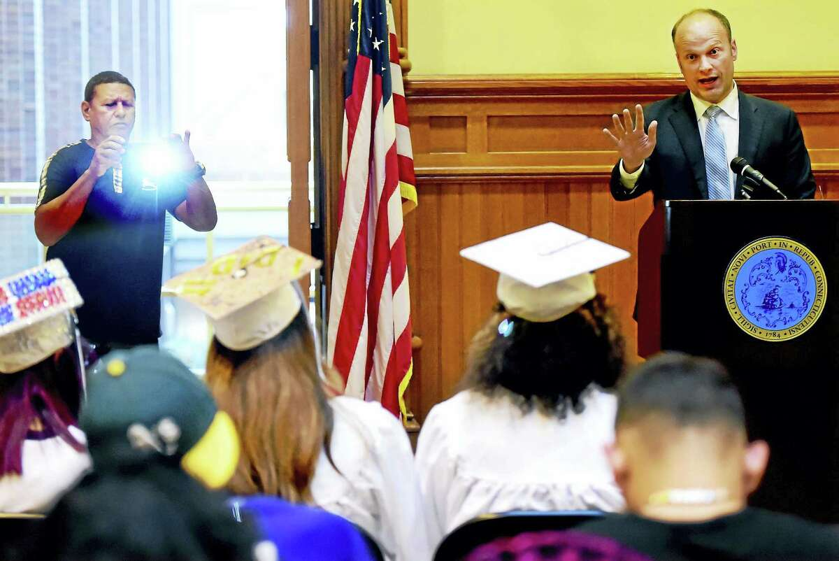 Benjamin Sanchez of New Haven takes a photograph of his granddaughter, Hillhouse High School graduate Elianis Rivera Sanchez, as New Haven Superintendent of Schools Garth Harries, right, shares words of encouragement during an Appreciation Ceremony at City Hall Friday.