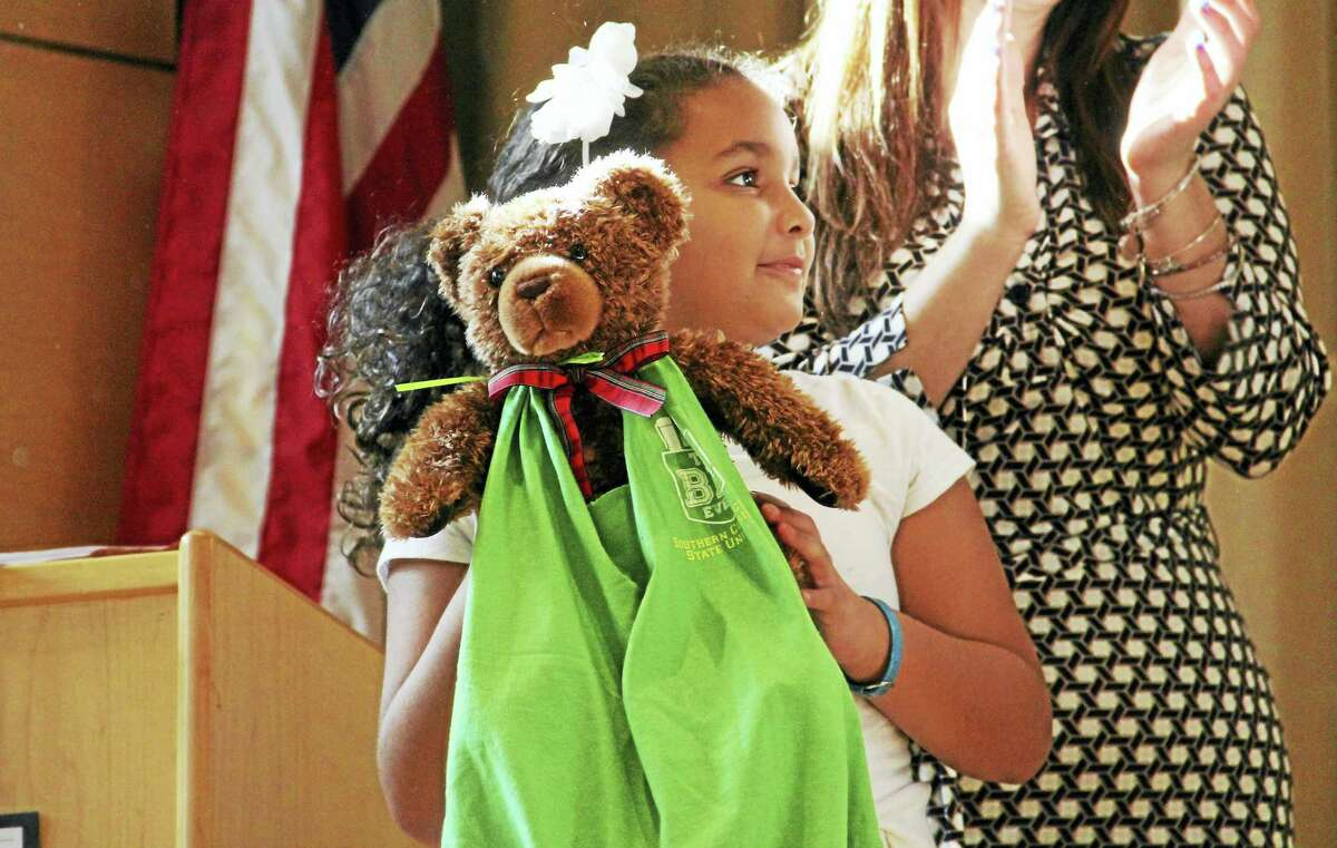 King-Robinson Interdistrict Magnet School third-grader Jayla Johnson holds up one of the care bags she and her classmates made for children at Yale New Haven Children's Hospital Child Life program, during a ceremony Friday at the school's auditorium.