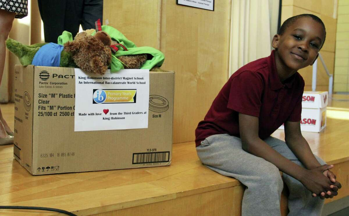 King-Robinson Interdistrict Magnet School third-grader Antoine Williams poses next to a box full of care packages made by him and his classmates before the start of a ceremony Friday.