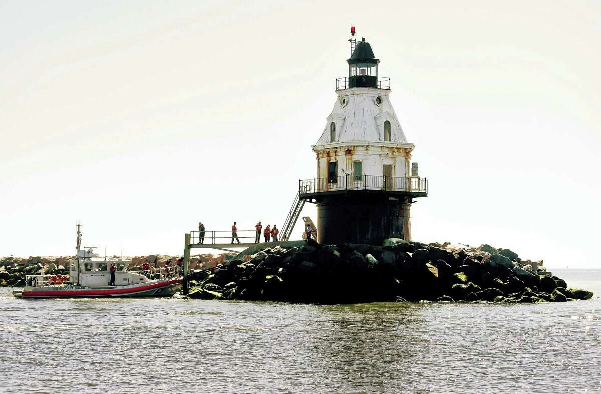 Prospective bidders are brought to the Southwest Ledge Lighthouse in New Haven Harbor on a Coast Guard boat for a visit Tuesday.