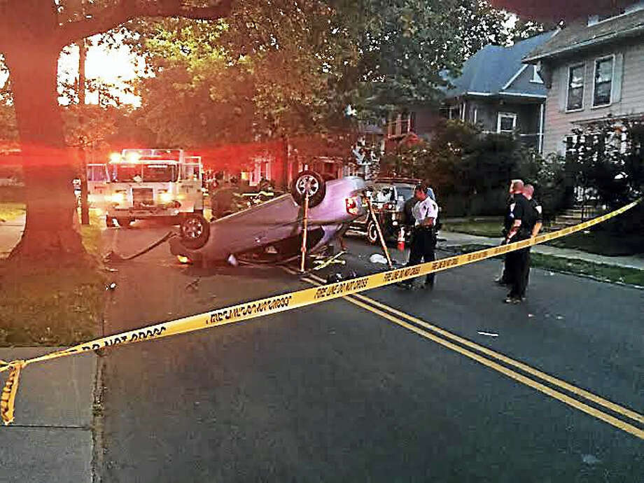 A car flipped onto its roof Tuesday evening on Willow Street in New Haven. Photo: Brian Zahn — New Haven Register