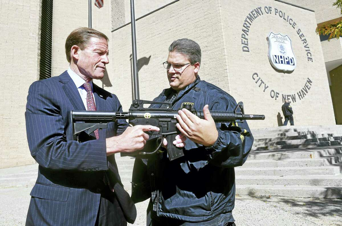 U.S. Sen. Richard Blumenthal, D-Conn., left, talks with New Haven police Lt. Herbert Johnson while holding a paintball rifle before a press conference in front of the New Haven Police Department Monday.