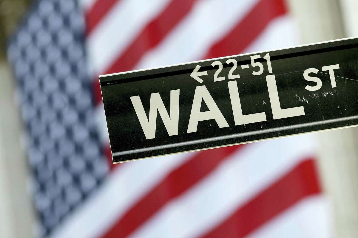FILE - In this Tuesday, Sept. 8, 2015, file photo, a Wall Street street sign is framed by an American flag hanging on the facade of the New York Stock Exchange. Global stock markets rose Tuesday, Aug. 9, 2016, as slack Chinese consumer price figures stoked expectations of more stimulus policies. Oil prices rose further after reports of a new OPEC meeting.