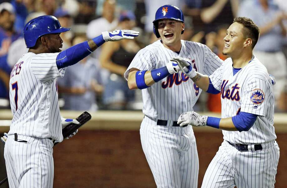 Jose Reyes, left, Brandon Nimmo, center, celebrate after Wilmer Flores, right, hit a three-run home run during the fifth inning on Thursday. Photo: Kathy Willens — The Associated Press   / AP