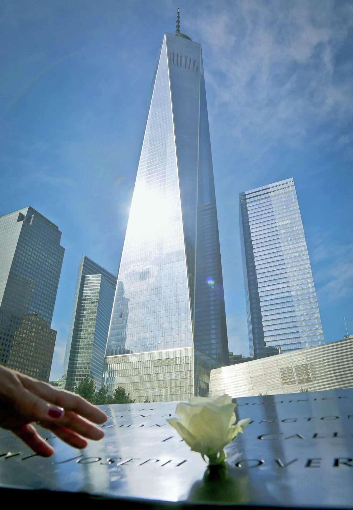 A visitor reaches to touch a name engraved at the Sept. 11 memorial site to remember the victims of the 2001 attacks on the World Trade Center on Thursday.