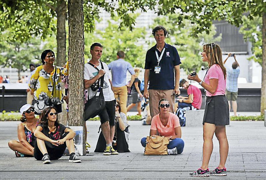 Jean Nebbia, far right, a schoolteacher from Oakland, N.J., talks with visitors to the Sept. 11 memorial site, Thursday Aug. 11, 2016, in New York. Nebbia serves as a volunteer tour guide, organized by the private nonprofit 9/11 Tribute Center, to tell tours about her brother Steven Schlag, a partner at Cantor Fitzgerald, who was killed in the Sept. 11 attacks on the World Trade Center. Photo: AP Photo/Bebeto Matthews