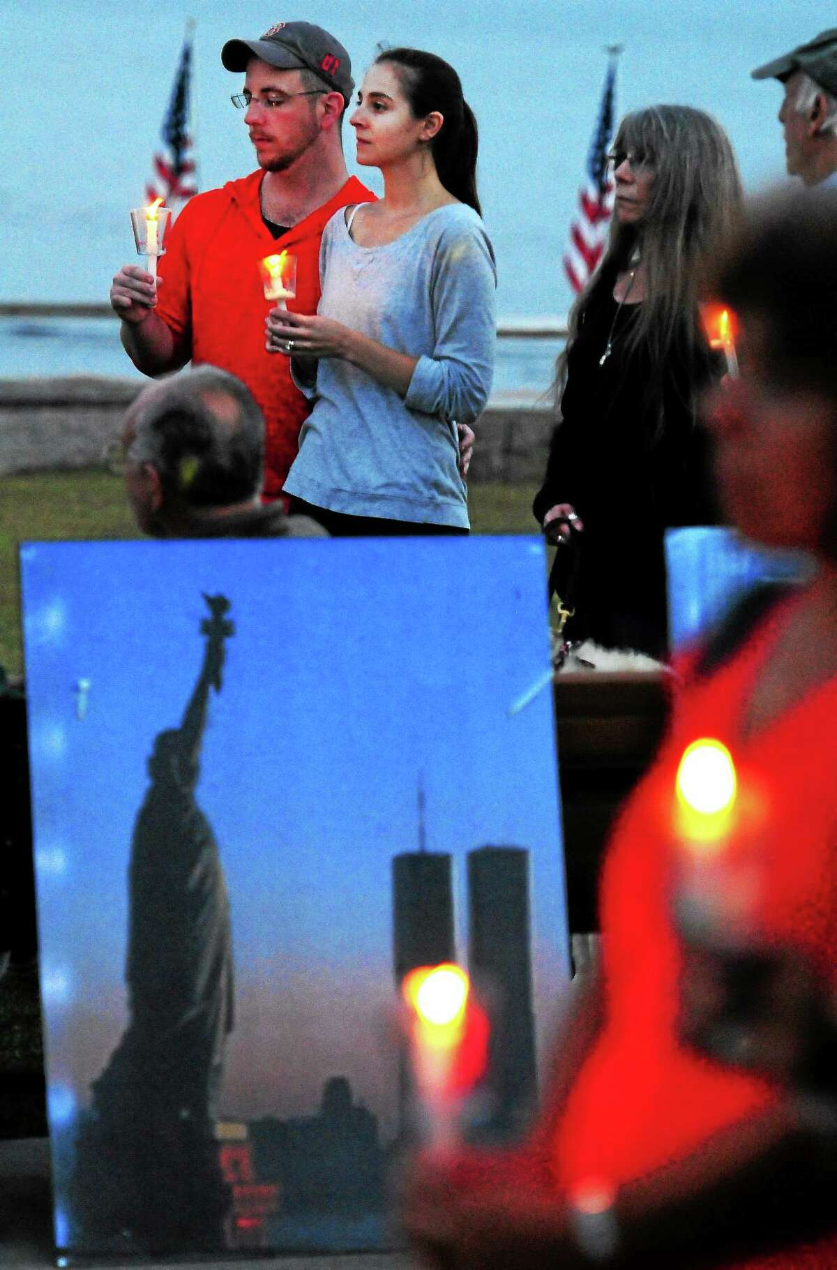 Pat Leigh, top left rear, with his wife, Amanda, center, and his mother, Linda Leigh, fourth from left, all of West Haven, during the City of West Haven's 13th anniversary of 9/11 Candlelight Vigil and Wreath Laying Ceremony in 2014 at the Richard S. Gabrielle Memorial.