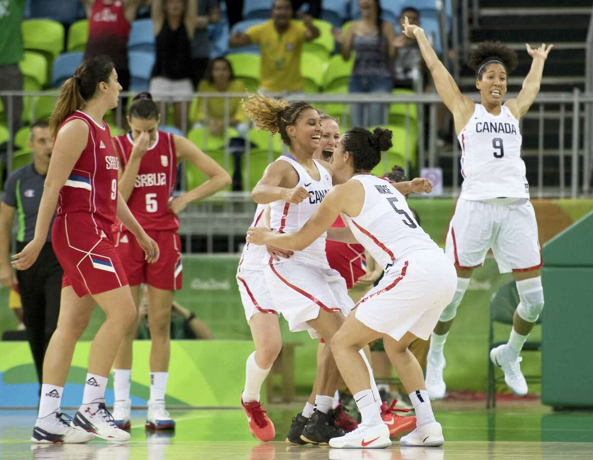 Members of the Canadian women's basketball team celebrate their win over Serbia on Monday.