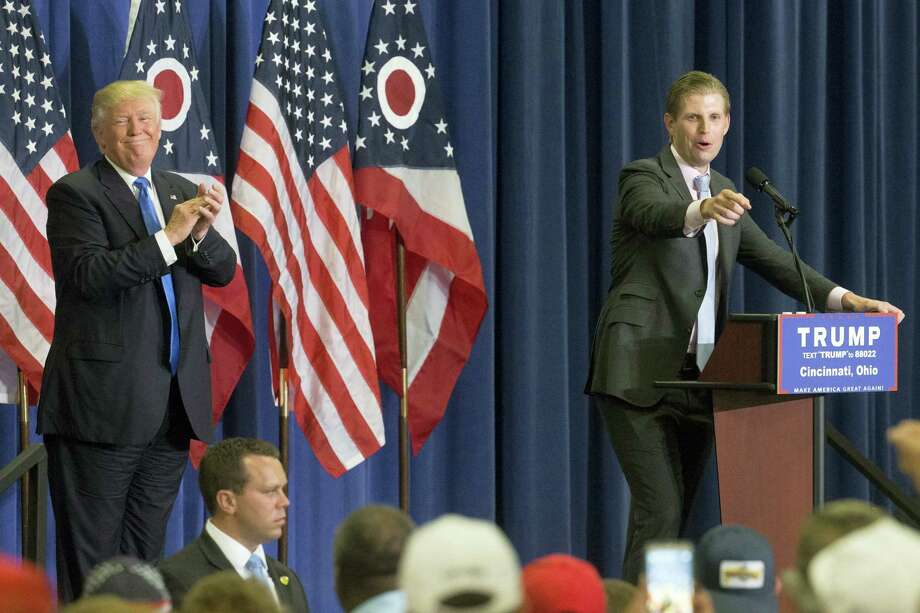 Republican presidential candidate Donald Trump, left, applauds as his son Eric Trump, right, speaks during a campaign rally at the Sharonville Convention Center on July 6, 2016 in Cincinnati. Photo: AP Photo/John Minchillo   / AP