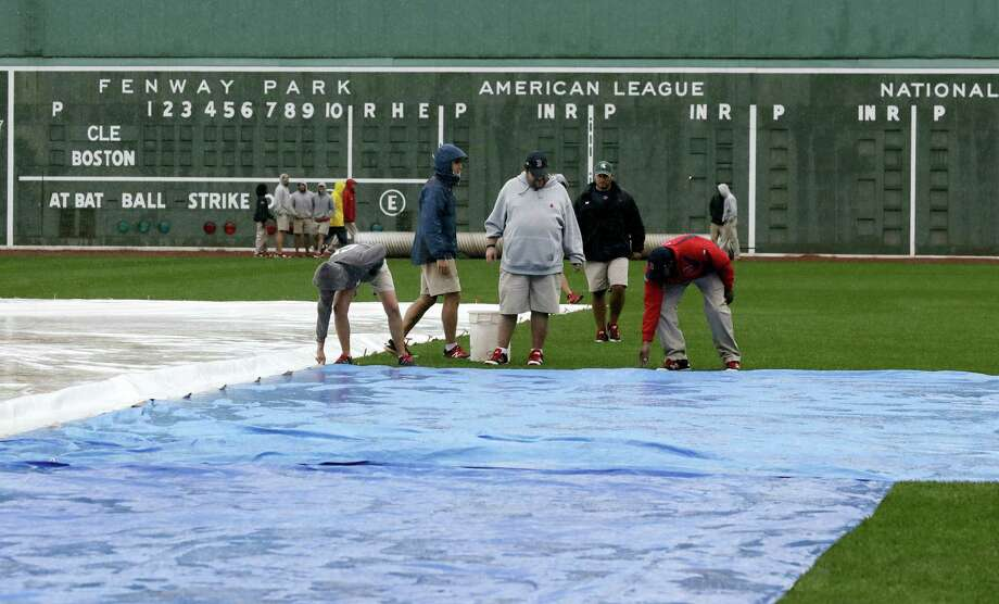 Grounds crew workers secure a tarp at Fenway Park, Sunday in Boston. Photo: Charles Krupa — The Associated Press   / Copyright 2016 The Associated Press. All rights reserved.