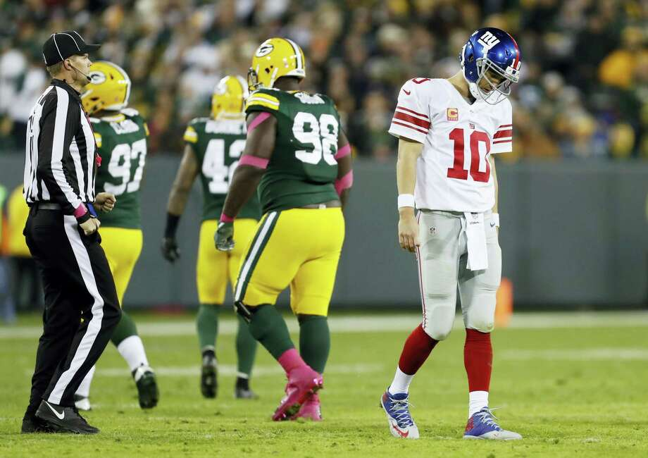 Eli Manning walks off the field after an incomplete pass during the second half on Sunday. Photo: Matt Ludtke — The Associated Press   / FR155580 AP