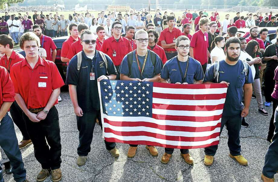 From left, electrical students Vincent Gabrielle, Matthew Main, Mark White and Logan Niper hold an American flag during a 9/11 memorial ceremony in front of Platt Technical High School in Milford Friday. Photo: Arnold Gold — New Haven Register