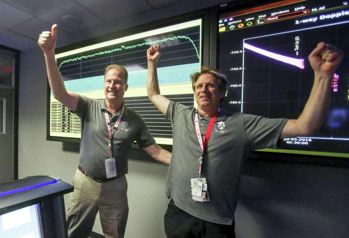 Scott Bolton, right, and Michael Watkins react in Mission Control at NASA's Jet Propulsion Laboratory as the solar-powered Juno spacecraft goes into orbit around Jupiter on Monday.