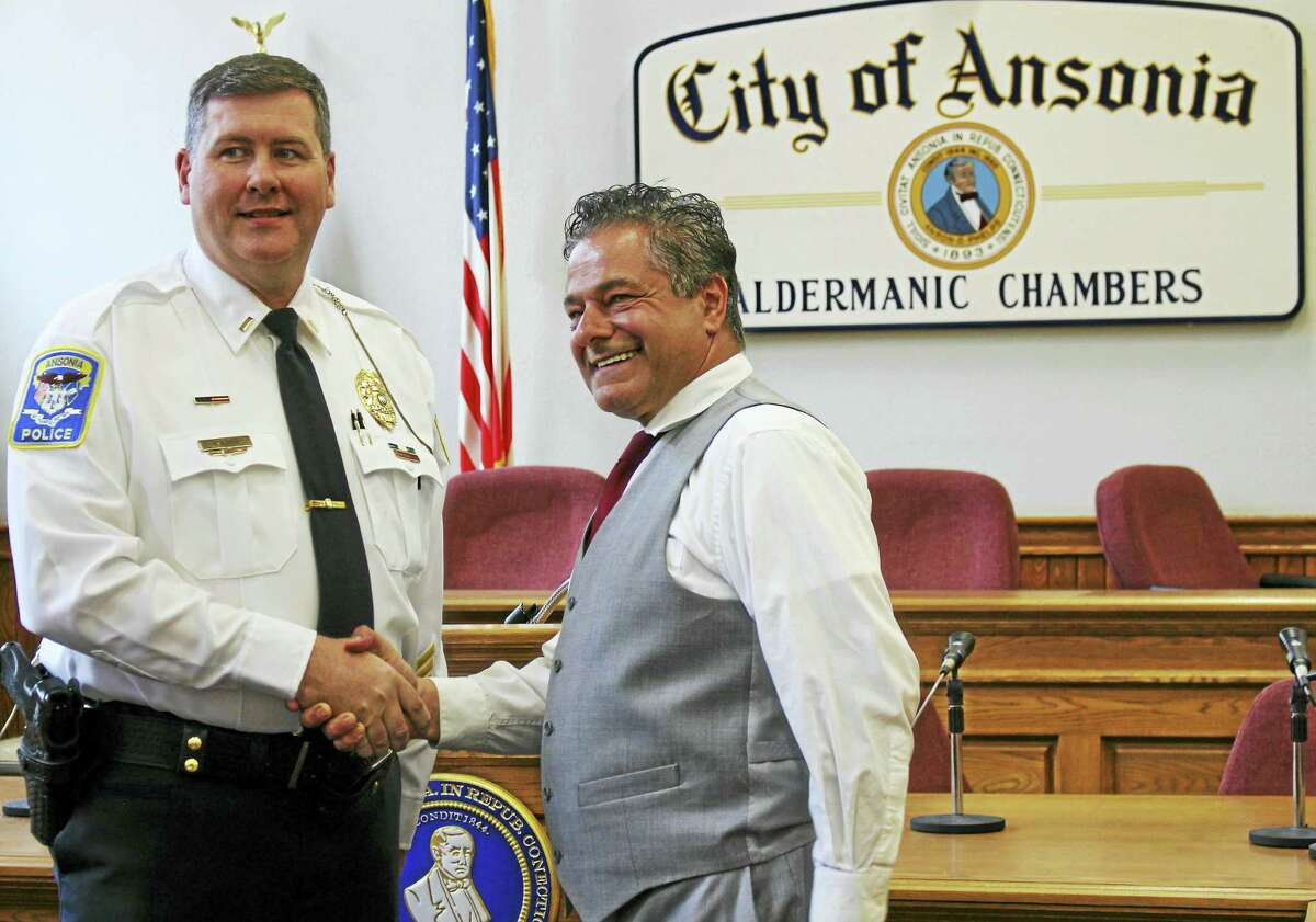 Patrick Lynch shakes hands with Ansonia Mayor David Cassetti after being sworn-in as a new lieutenant in the Ansonia Police Department.
