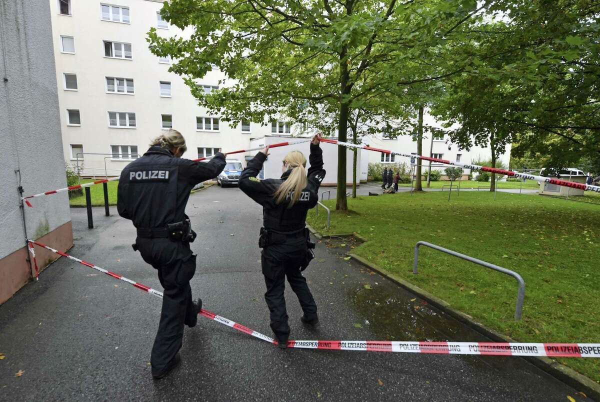 Two policewomen walk under a police cordon Oct. 9, 2016 that secures an apartment building in Chemnitz eastern Germany. German police search nationwide Sunday for a 22-year-old Syrian man believed to have been preparing a bombing attack, and were questioning a second Syrian man on suspicion he was involved in the plot.