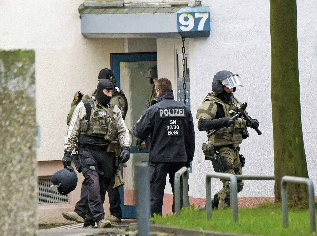 Police officers leave an apartment after detonations in the eastern city of in Chemnitz, Germany, Saturday, Oct. 8, 2016. German investigators found several hundred grams of explosives in an apartment they raided Saturday in the eastern city of Chemnitz as they sought a Syrian man suspected of planning a bombing attack. The suspect remained on the run but three contacts were detained and being questioned, police said.