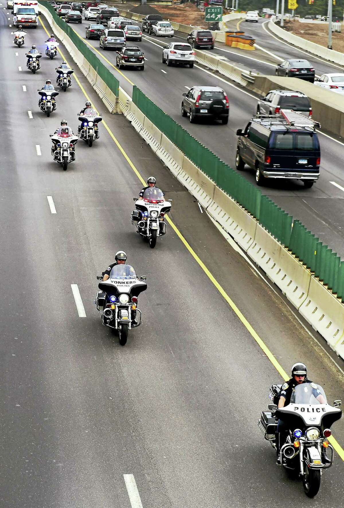 Peter Hvizdak —New Haven Register Police motorcycles escort an ambulance, top left, along northbound Interstate 95 Thursday as it transports seriously injured West Haven police Officer Mike Doyle to Gaylord Hospital from New York.