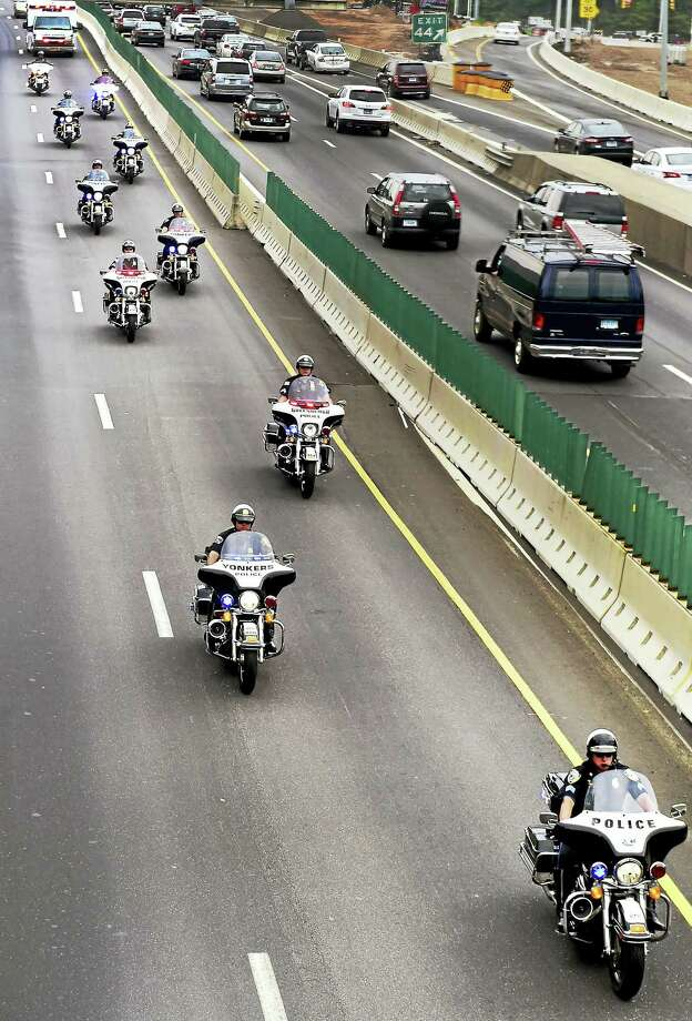Peter Hvizdak —New Haven Register   Police motorcycles escort an ambulance, top left, along northbound Interstate 95 Thursday as it transports seriously injured West Haven police Officer Mike Doyle to Gaylord Hospital from New York. Photo: ©2016 Peter Hvizdak / ?2016 Peter Hvizdak