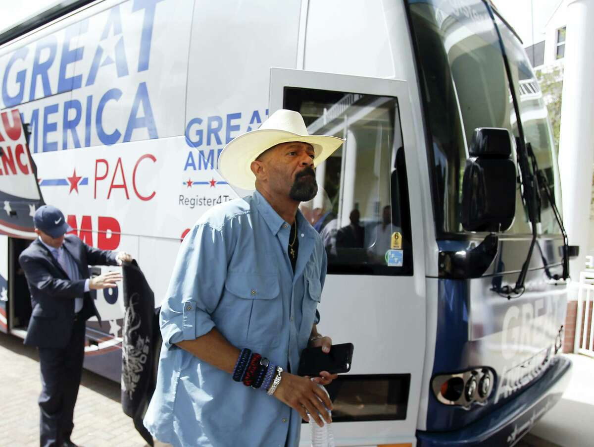 In this Monday, Sept. 12, 2016 photo, David A. Clarke Jr., Sheriff of Milwaukee County, Wis., and Donald Trump supporter, arrives on the Great America PAC bus for a town hall meeting in Lake Mary, Fla. The Great America PAC is rolling through battleground states, opening offices and registering voters. Presidential hopefuls often embark on bus tours to meet voters across the country. This time, a super PAC is standing in for Republican nominee Donald Trump. (AP Photo/John Raoux)