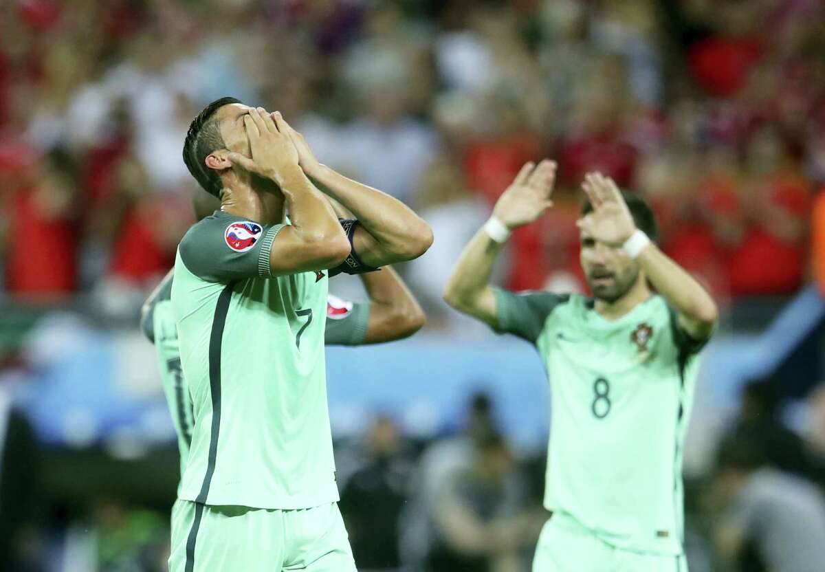 Portugal's Cristiano Ronaldo, left, celebrates winning the Euro 2016 semifinal soccer match against Wales, at the Grand Stade in Decines-Charpieu, near Lyon, France Wednesday.