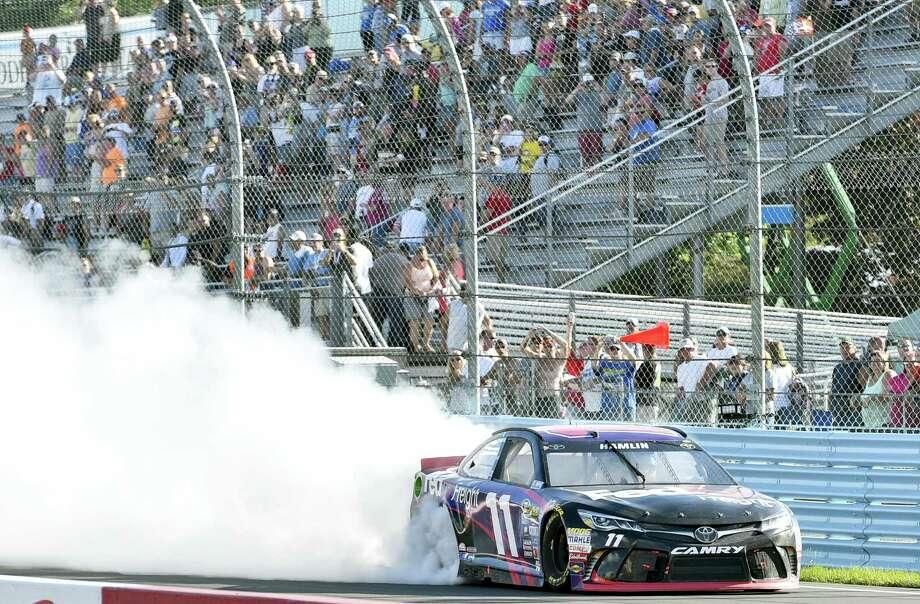 Denny Hamlin celebrates with a burnout after winning at Watkins Glen International on Sunday in Watkins Glen, N.Y. Photo: Derik Hamilton — The Associated Press   / FR170553 AP