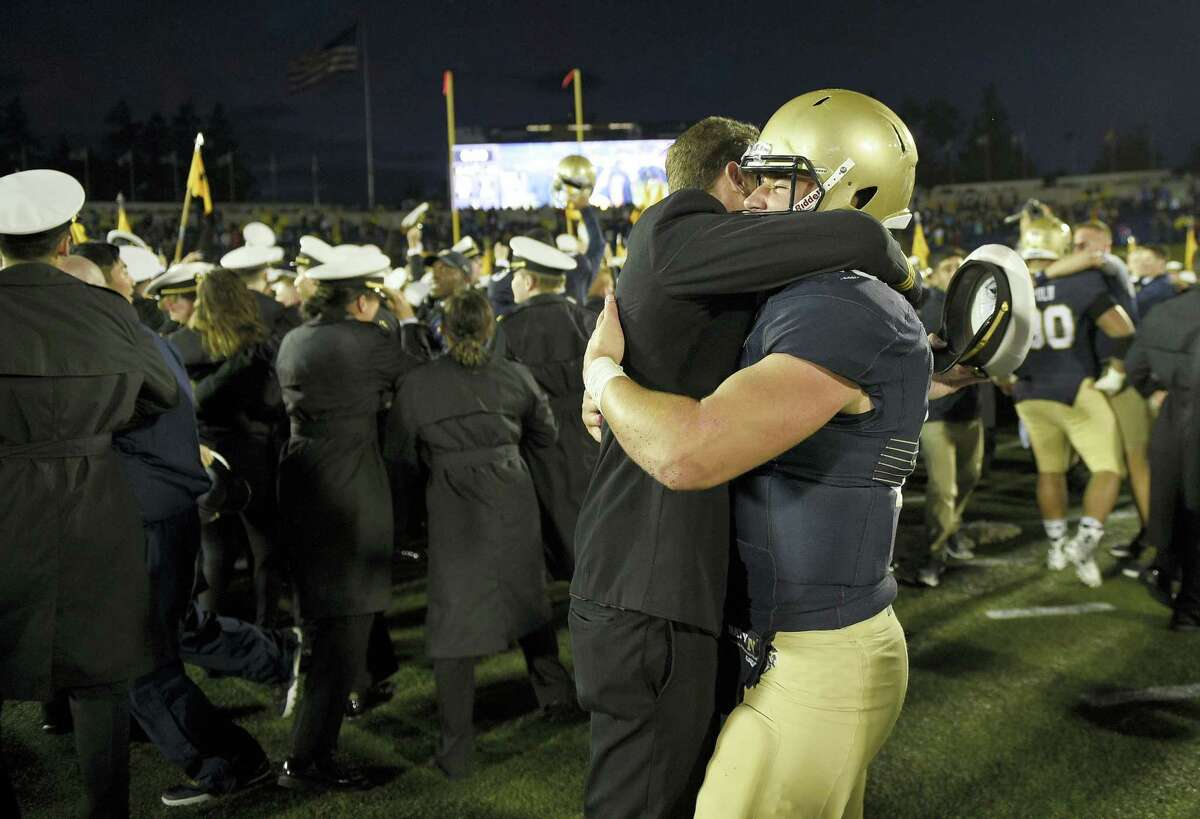 Navy quarterback Will Worth, right, gets a hug from a midshipmen after Saturday's win over Houston.