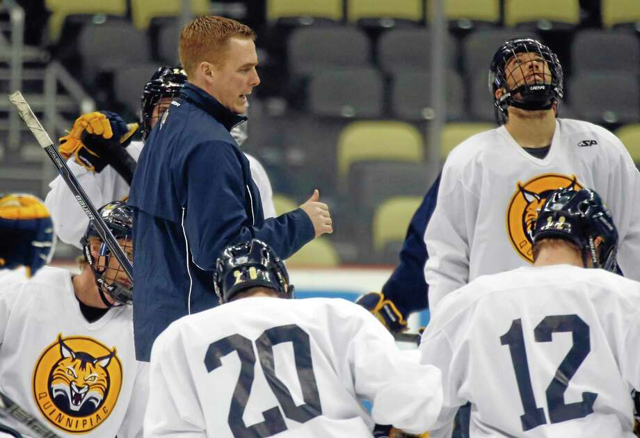 Quinnipiac coach Rand Pecknold, left, talks to his team between drills during NCAA college hockey practice at the Frozen Four, Friday, April 12, 2013, in Pittsburgh. Quinnipiac plays Yale in the championship game on Saturday. (AP Photo/Keith Srakocic) Photo: AP / AP