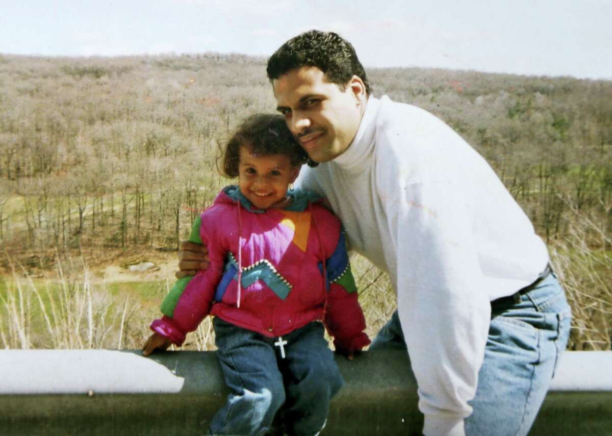 """This undated photo provided by Thea Trinidad shows her with her father, Michael Trinidad. Michael was a former high school wrestler who didn't flinch when his tomboy daughter did leaping moves off the furniture. In fact, """"he'd say, 'No, you're doing it wrong — let me show you,'"""" says Thea, 25, who lives in Tampa, Fla. She says she feels her father's spirit every time she goes into the ring. """"This one's for you, Dad,"""" she tells herself. """"Protect me out there."""""""