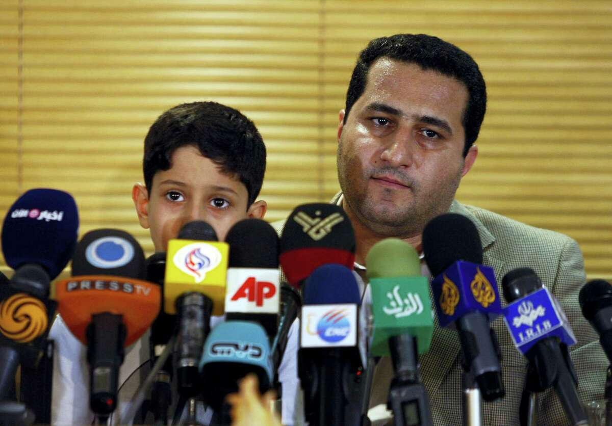 In this photo taken July 15, 2010, Shahram Amiri, an Iranian nuclear scientist attends a news briefing while holding his son Amir Hossein as he arrives at the Imam Khomeini airport just outside Tehran, Iran, after returning from the United States. Amiri, who was caught up in a real-life U.S. spy mystery and later returned to his homeland and disappeared, has reportedly been executed under similarly mysterious circumstances.