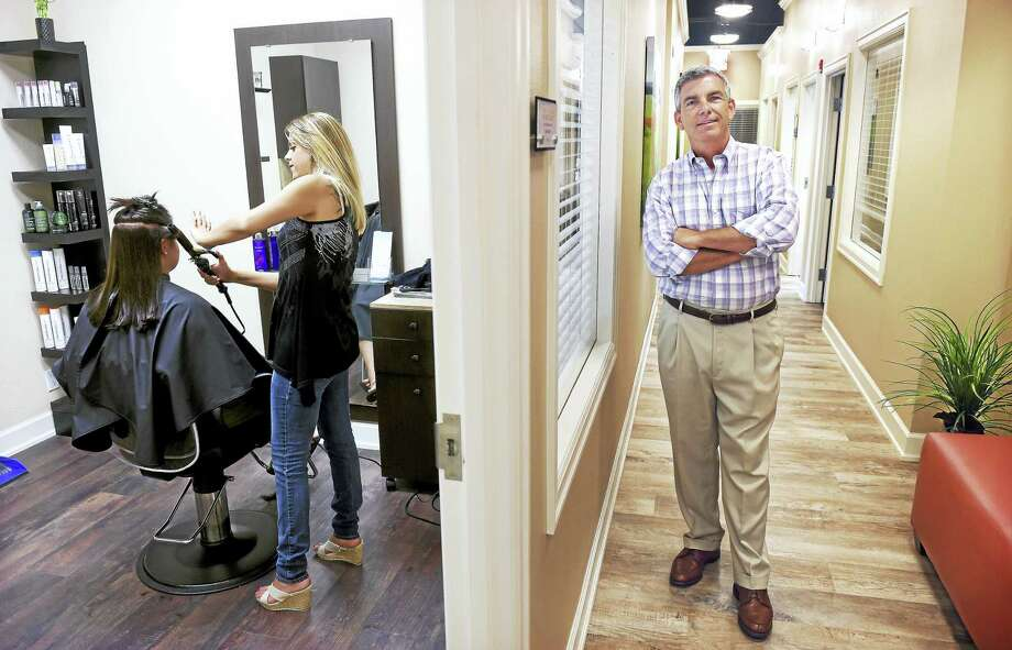 Rachel Saint (far left) of Sandy Hook has her hair done by Melanie Leonard in one of the suites at Salons by JC in Milford on 8/3/2016.  Leonard rents a suite for her business, Hair Artistry by Melanie.  At right is Jim McGuiness, co-owner of Salons by JC. Photo: Arnold Gold-New Haven Register