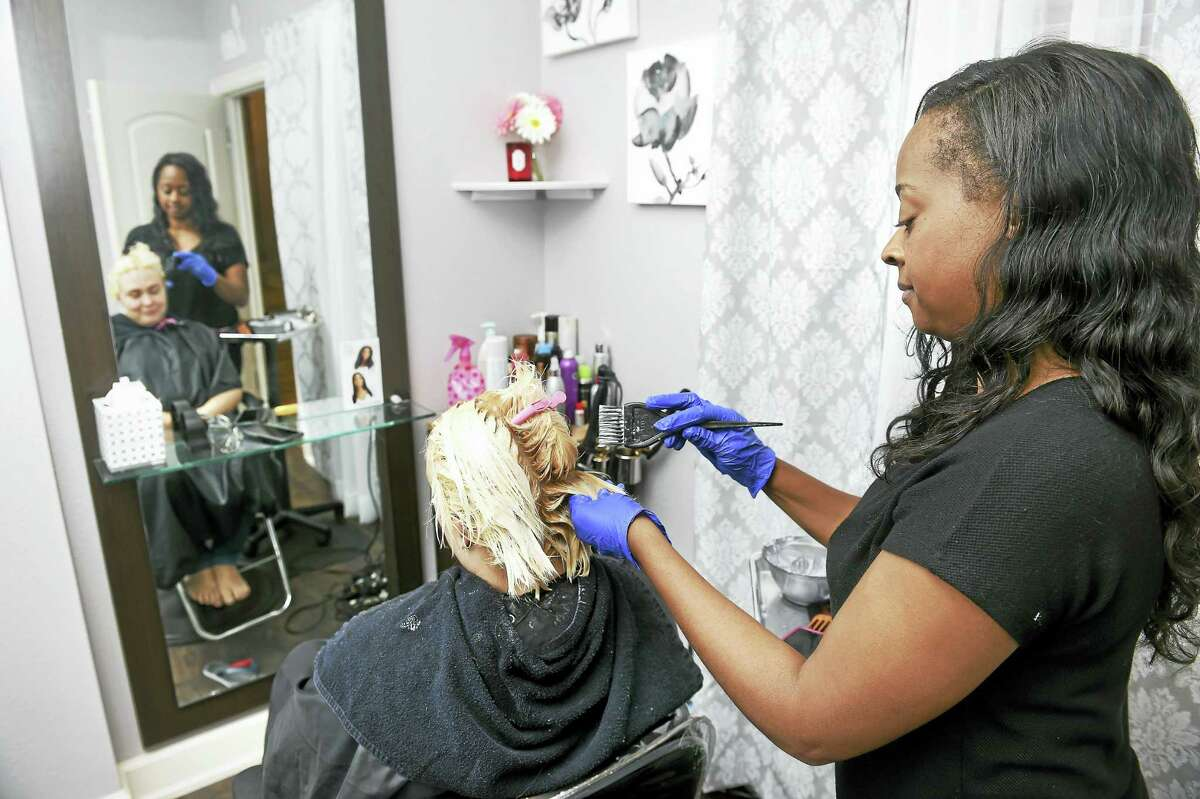 Lara DaCosta (left) of Bridgeport has her hair done by Charlene Lewis in one of the suites at Salons by JC in Milford on 8/3/2016. Lewis rents a suite for her business, Beauty by Charlene.