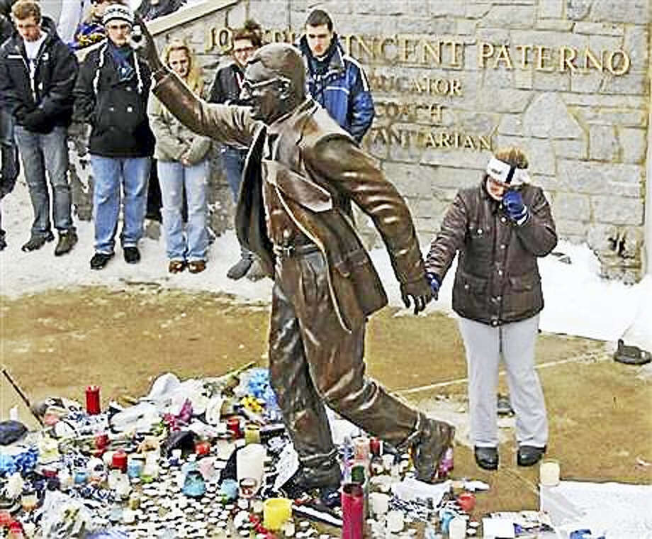In this Jan. 22, 2012, file photo, a woman pays her respects at a statue of former Penn State football coach Joe Paterno outside Beaver Stadium on the Penn State University campus in State College, Pa. More than 200 former Penn State football players are petitioning university leaders to return the bronze statue of Paterno that stood outside the school's football stadium. The statue of the late football coach was removed in 2012. The players sent a letter Tuesday, July 5, 2016, to the board of trustees and Penn State President Eric Barron calling for the statue's return. Photo: AP Photo/Gene J. Puskar, File