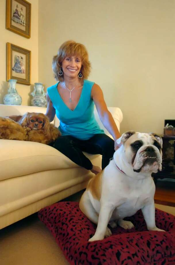 Elaine Doran in her home studio where she creates Puppy Hugger & Kitty Cats Too dog and cat beds on Tuesday, June 8, 2010. Chelsea, a Cavalier King Charles spaniel, 6, left and Winston, 1, English Bull Dog enjoy the beds. Photo: Helen Neafsey / Greenwich Time