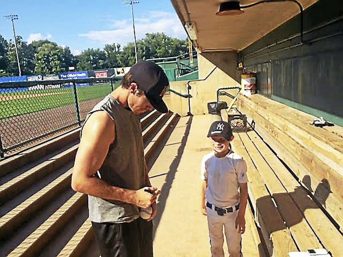 Casey Frawley signs an autograph for a young fan prior to a New Britain Bees game.