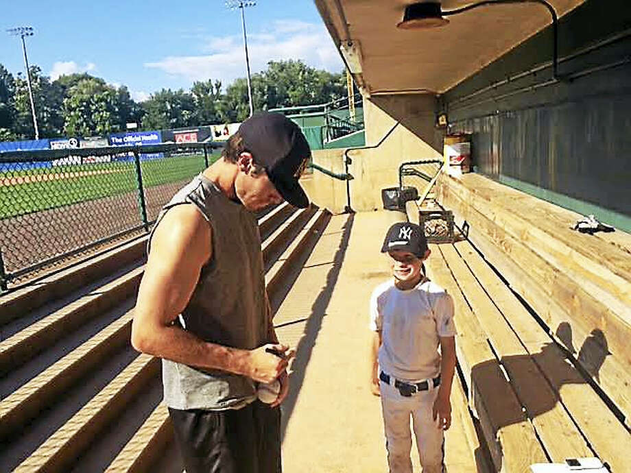 Casey Frawley signs an autograph for a young fan prior to a New Britain Bees game. Photo: David Borges — Register