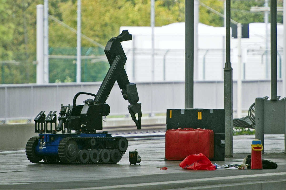A remotely controlled bomb disposal robot approaches a red suitcase on a platform at the Chemnitz Central Station in eastern Germany, Saturday, Oct. 8, 2016. German investigators found several hundred grams of explosives in an apartment they raided Saturday in the eastern city of Chemnitz as they sought a Syrian man suspected of planning a bombing attack.