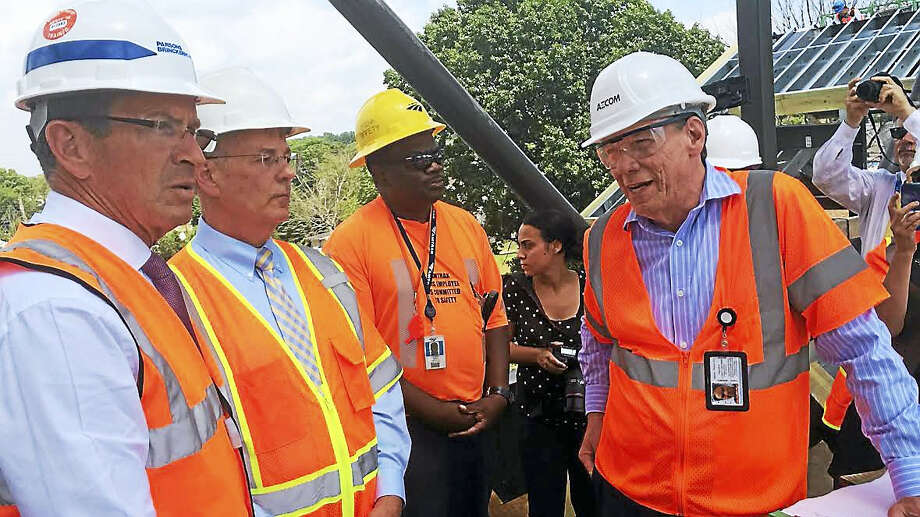 Gov. Dannel Malloy, far left, and State Transportation Commissioner James Redeker, second from left, listen Wednesday as construction officials explain the work being done around the new Wallingford train station. Photo: LUTHER TURMELLE — NEW HAVEN REGISTER
