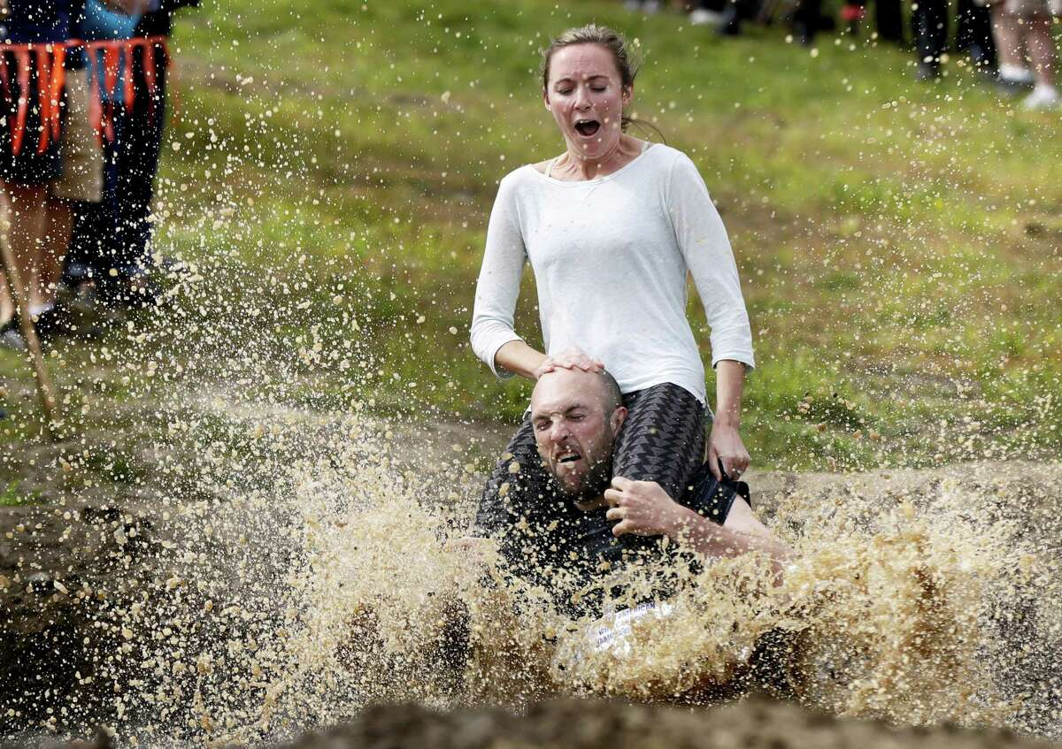 Peter Ver Ploeg carries Virginia Petrovek through the mud pit during the North American Wife Carrying Championship, Saturday, Oct. 8, 2016, at the Sunday River Ski Resort in Newry, Maine. The couple, from Portland, Maine, has been married for one year.